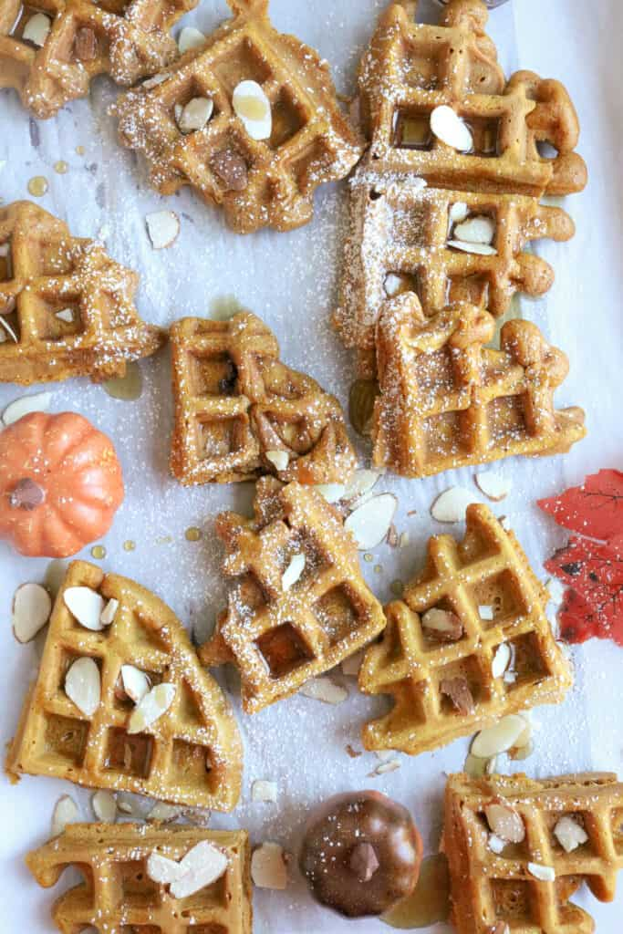 Waffle pieces on white background with walnuts on top with syrup.