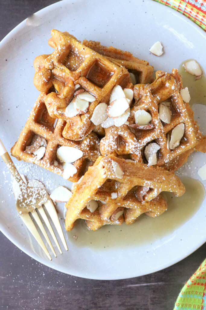 Pieces of waffles on gray plate topped with walnuts and syrup.