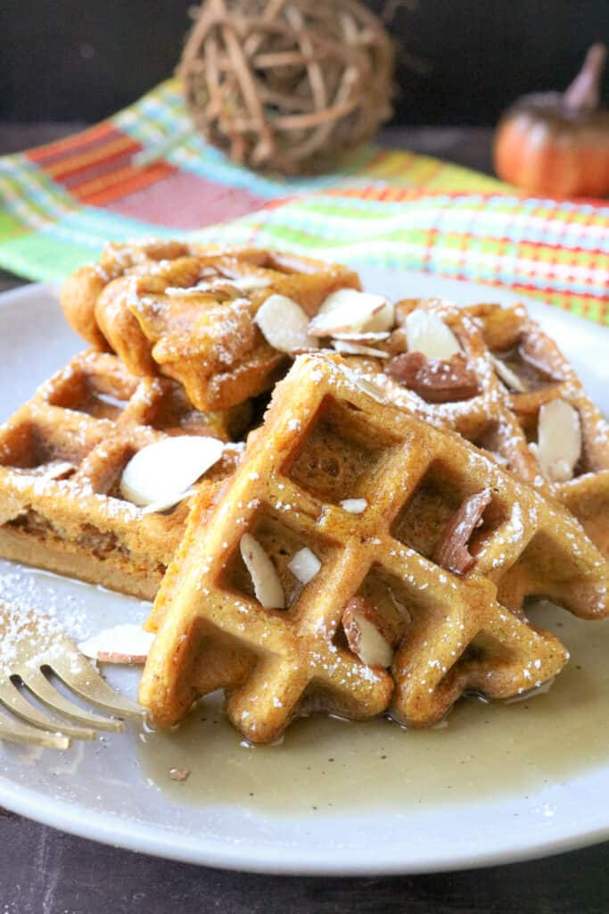 Pumpkin waffles on plate topped with syrup
