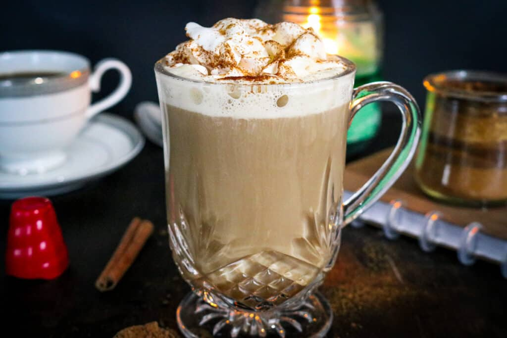 latte in clear mug topped with whipped cream and cinnamon