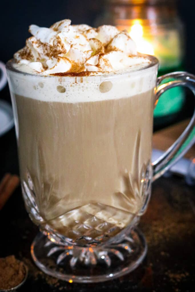 PUMPKIN LATTE IN CLEAR MUG TOPPED WITH WHIPPED CREAM AND CINNAMON