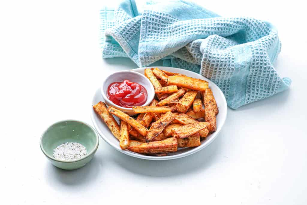 yuca fries in white plate with ketchup, salt and pepper and kitchen towel