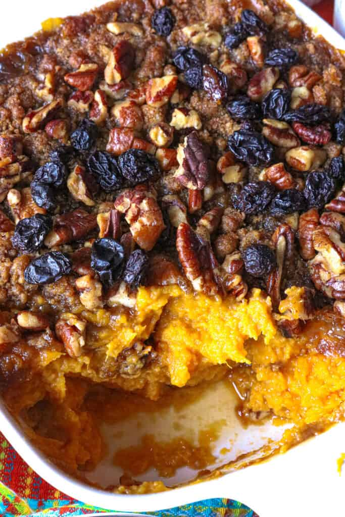 sweet potato casserole in white baking dish topped with raisins