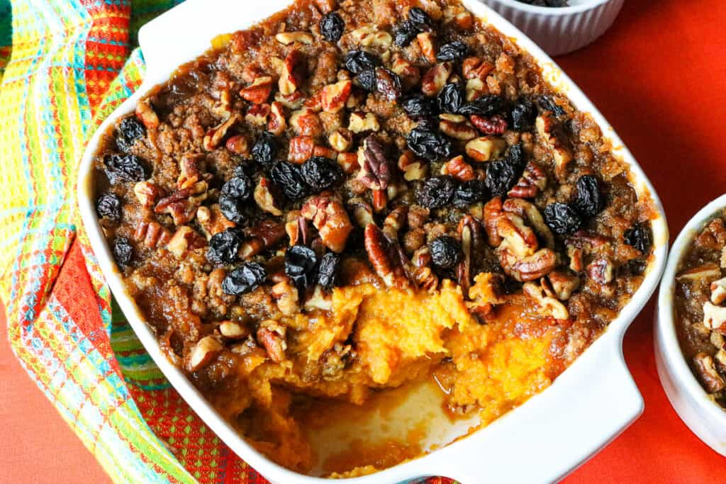 air fryer sweet potato casserole in white baking dish topped with raisins