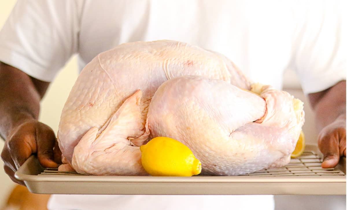 Haitian turkey - hand holding a turkey on a tray with lemon