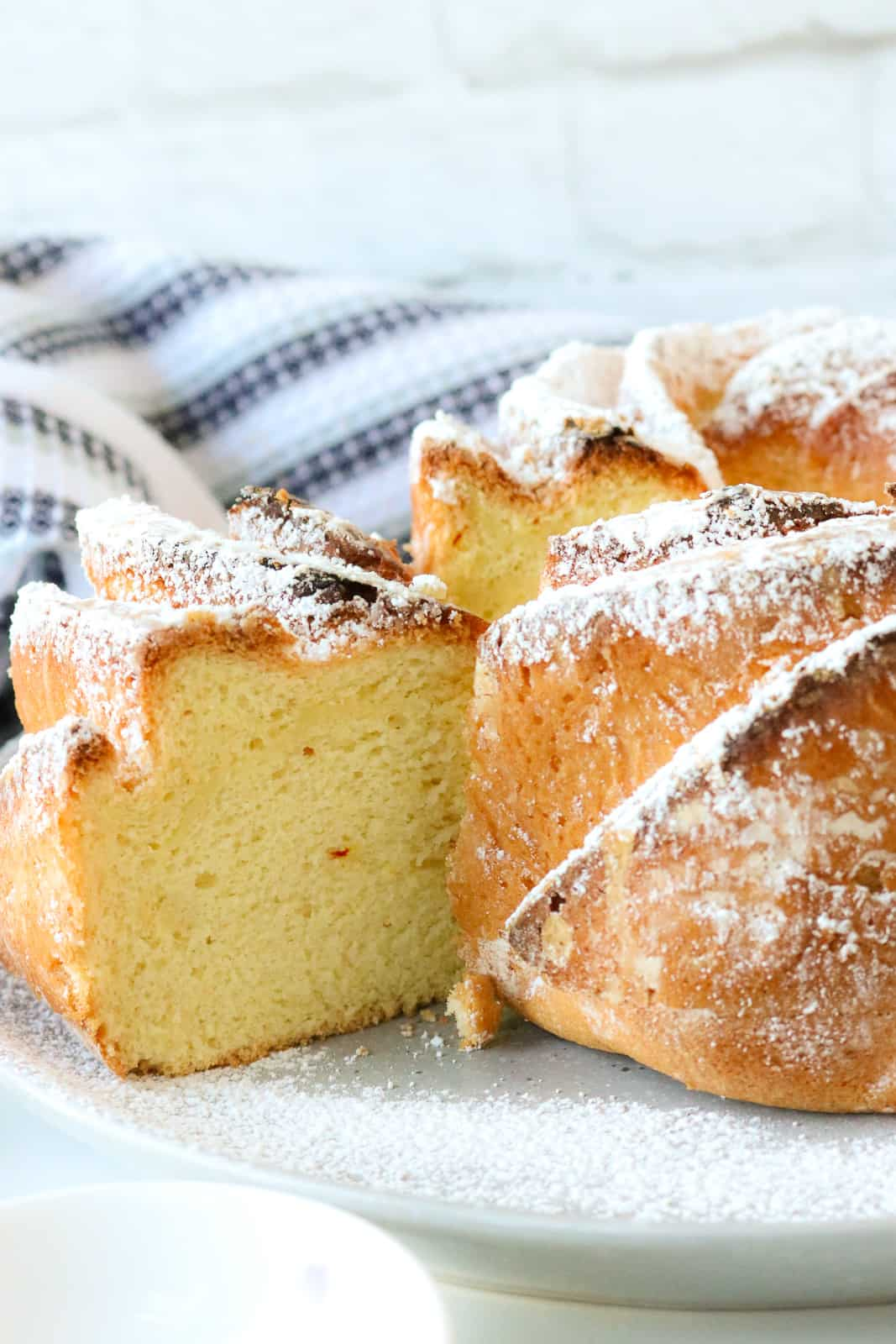 Saffron cake with slice cut out on a plate topped with powdered sugar
