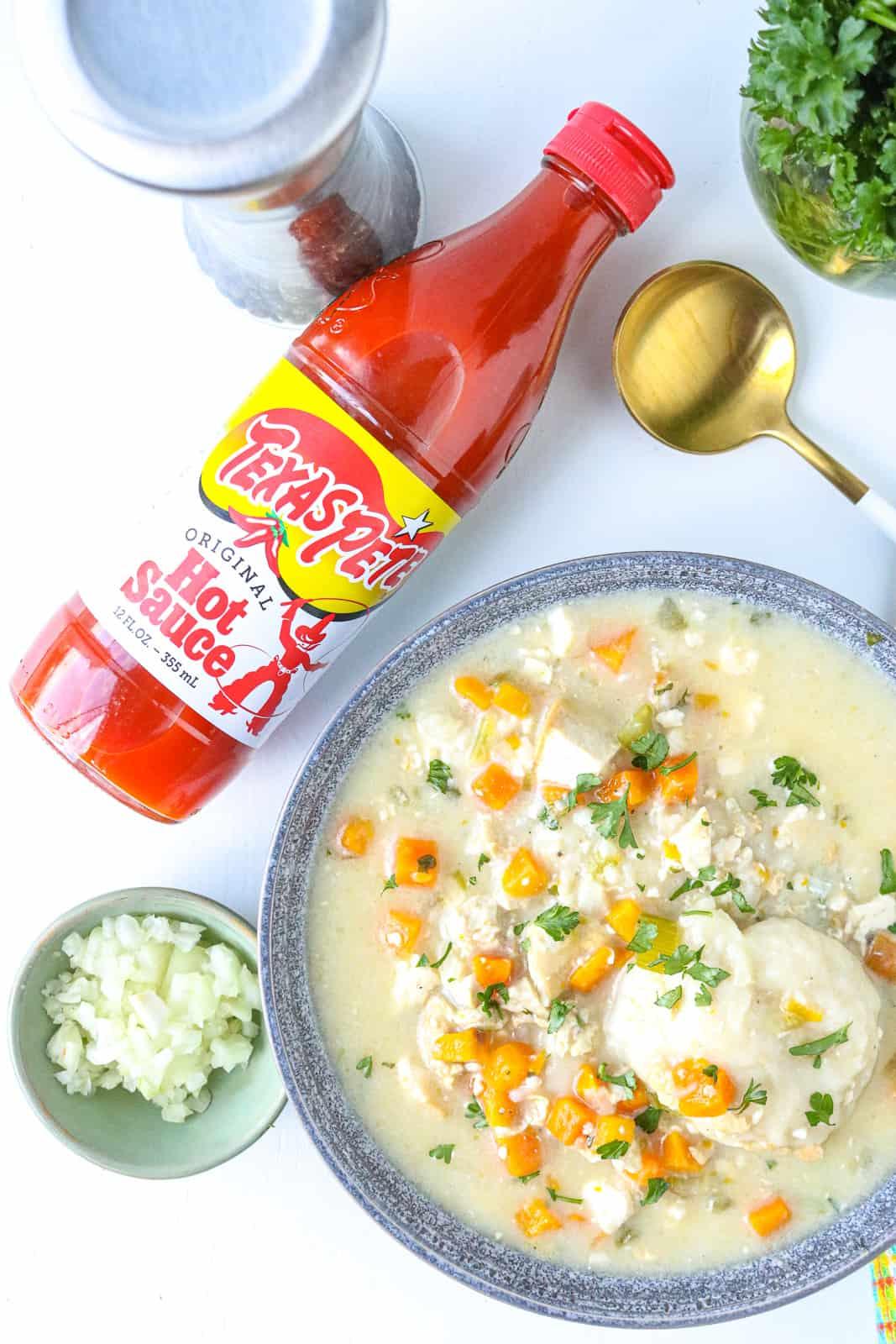 hot sauce next to chicken and dumplings soup