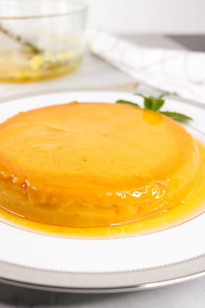Instant pot flan on white plate with syrup around the  flan. Mint leaves on the side and bowl in the background