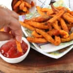 hand dipping fries in ketchup on wooden cutting obard