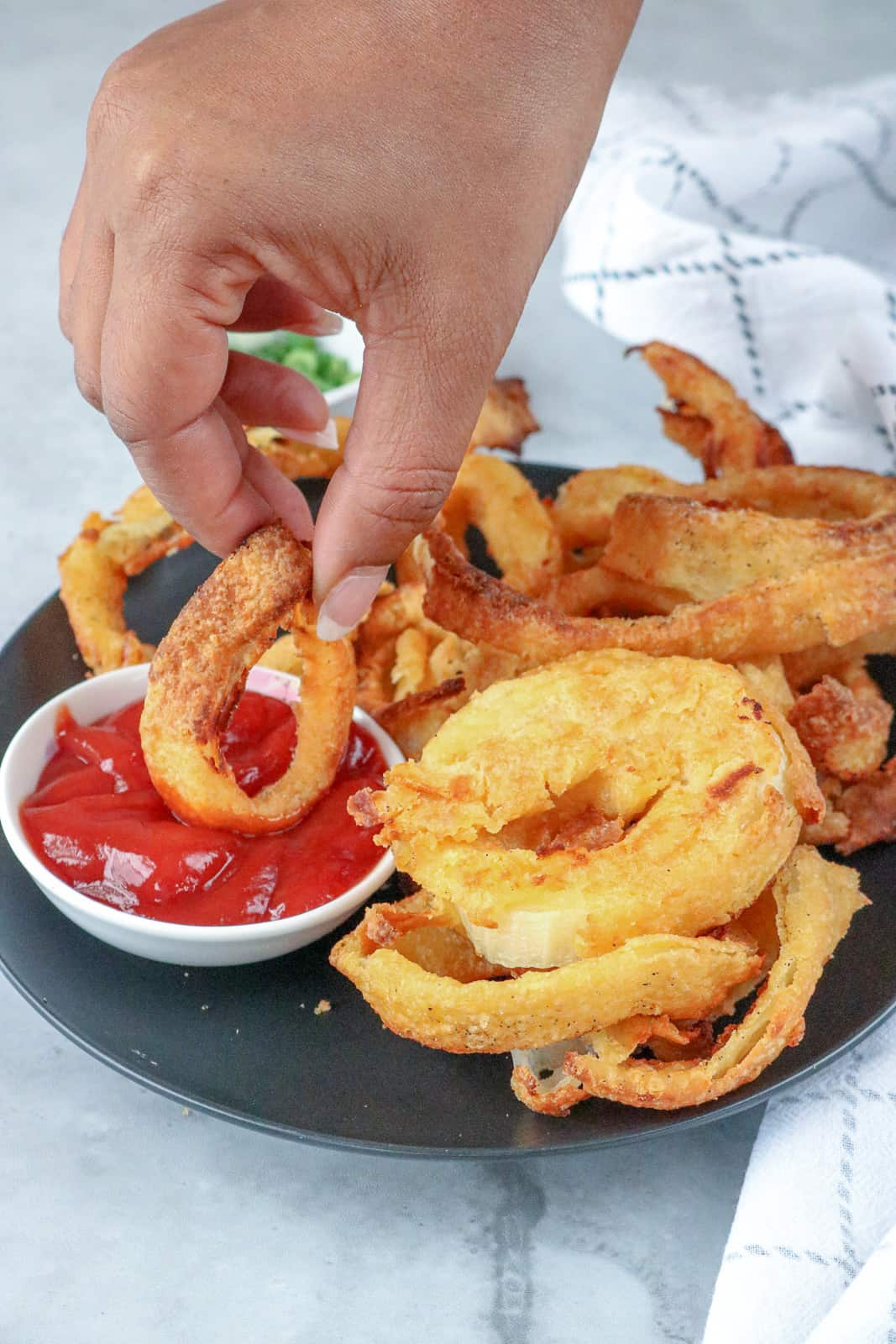 Hand dipping onion ring in ketchup