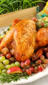 Whole turkey on a bed of grapes, apples, fresh herbs on a white platter