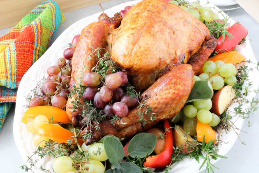 Whole bird on a bed of grapes, apples, fresh herbs on a white platter