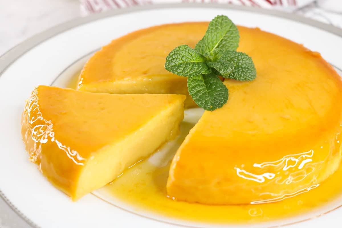 Flan cut out with mint on top on white plate