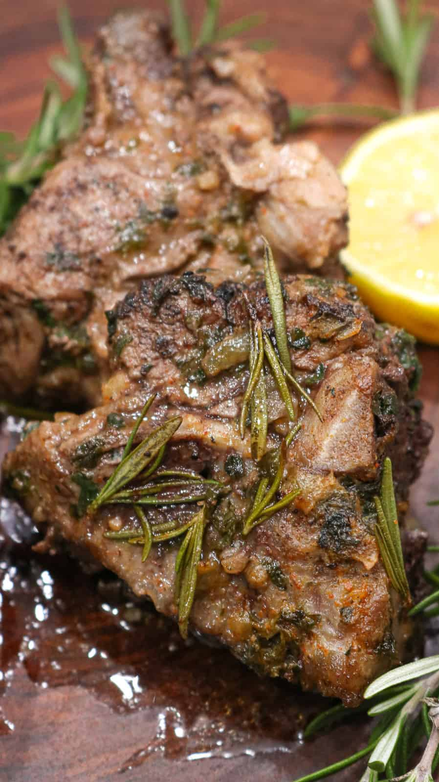 Baked lamb chops on wooden board topped with rosemary