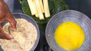 breadcrumbs, cheese stick and eggs in gray bowl