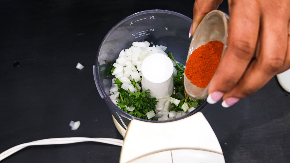 Pouring cayenne pepper into the food processor over herbs and onions