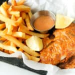 fish and fries with lemon wedges on top of parchment paper