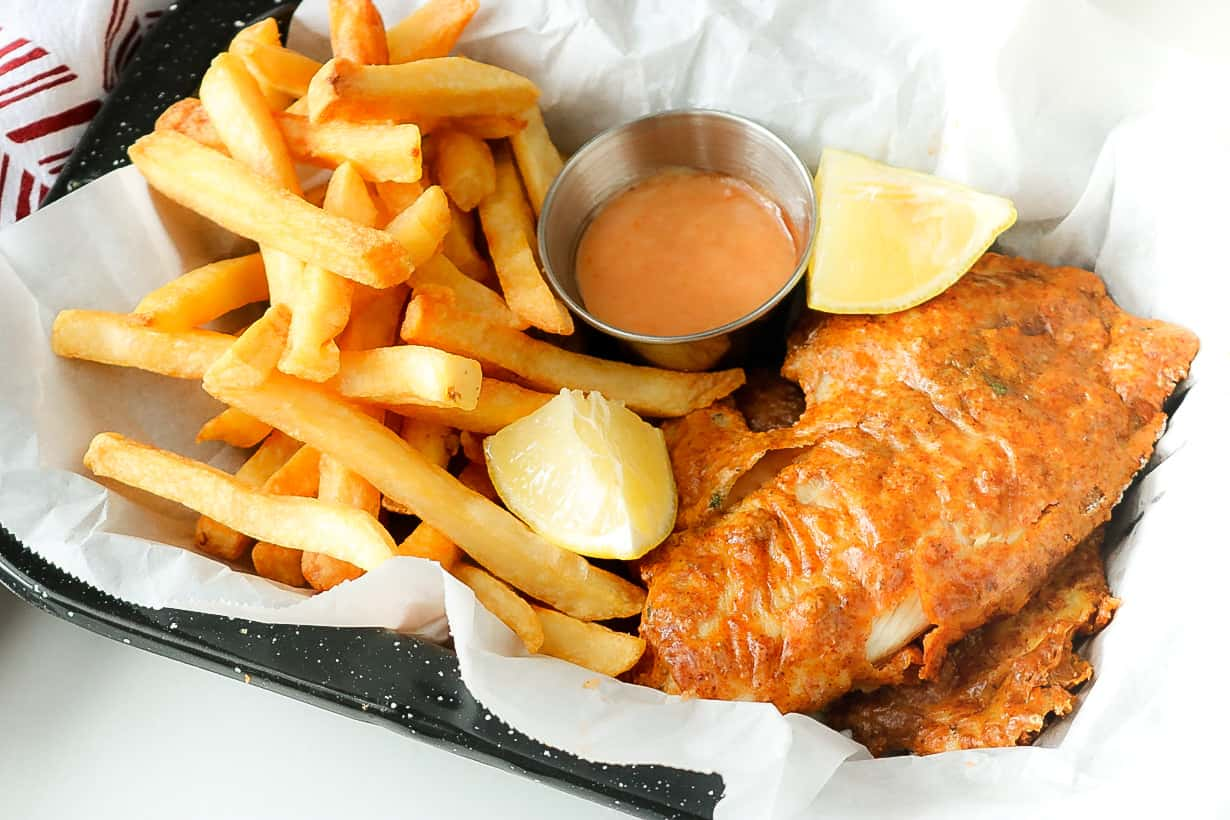 fish and chips with lemon wedges on top of parchment paper