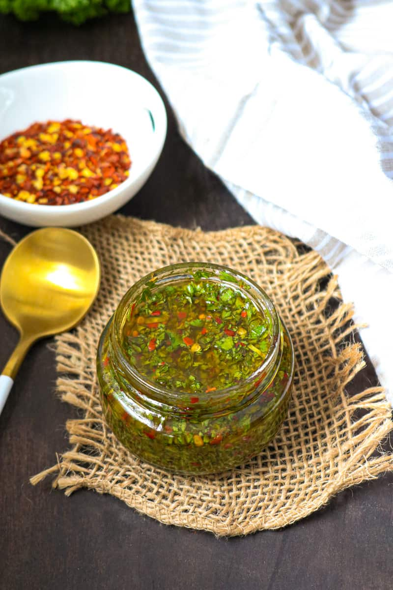 CHIMICHURRI SAUCE in glass jar with peppers in white bowl