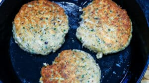 3 salmon burgers cooking in skillet