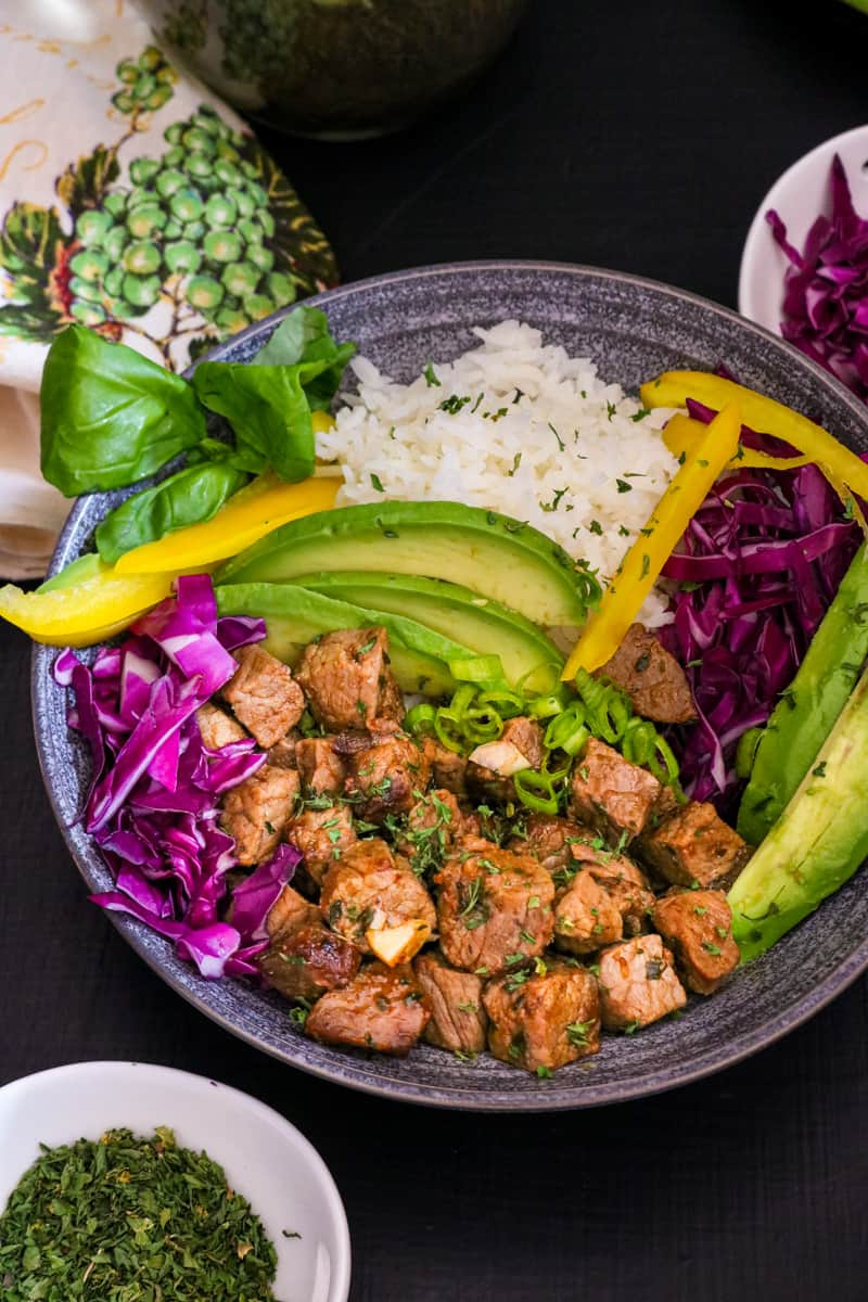 steak bites, rice, veggies on gray plate