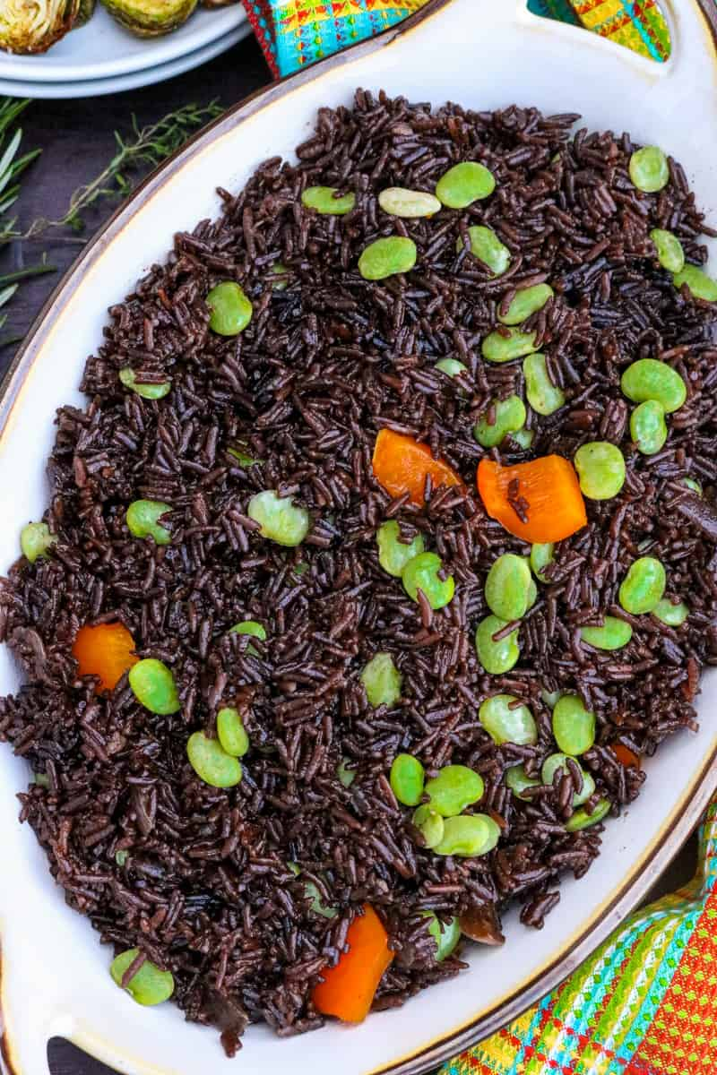 haitian black rice topped with green peas and orange bell peppers