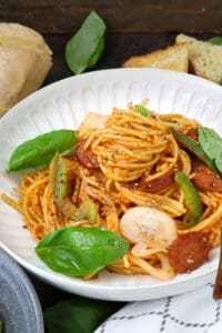 Haitian spaghetti topped with peppers, basil, and onions on white bowl