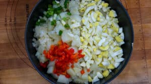 eggs, potatoes, green beens, red bell peppers, and onions in black bowl