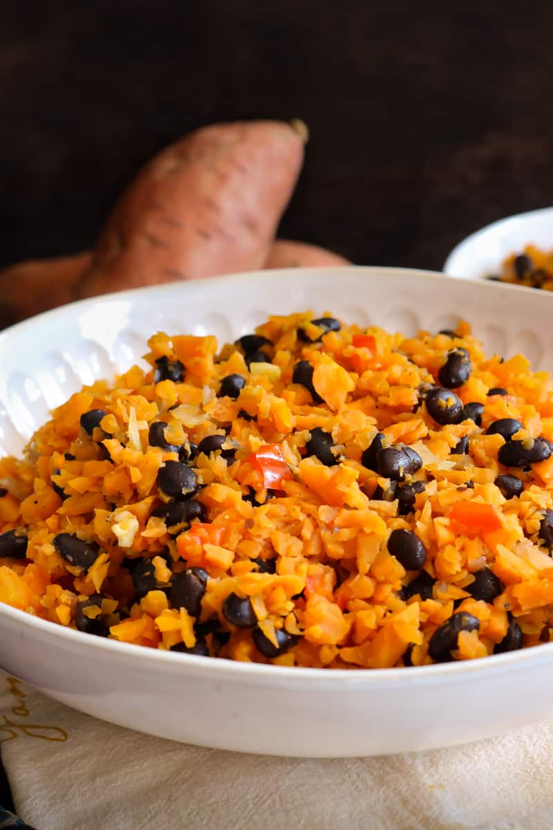 vertical view of sweet potato rice in white bowl and raw sweet potatoes in the back