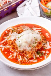 lasagna in white plate with sauce and cheese