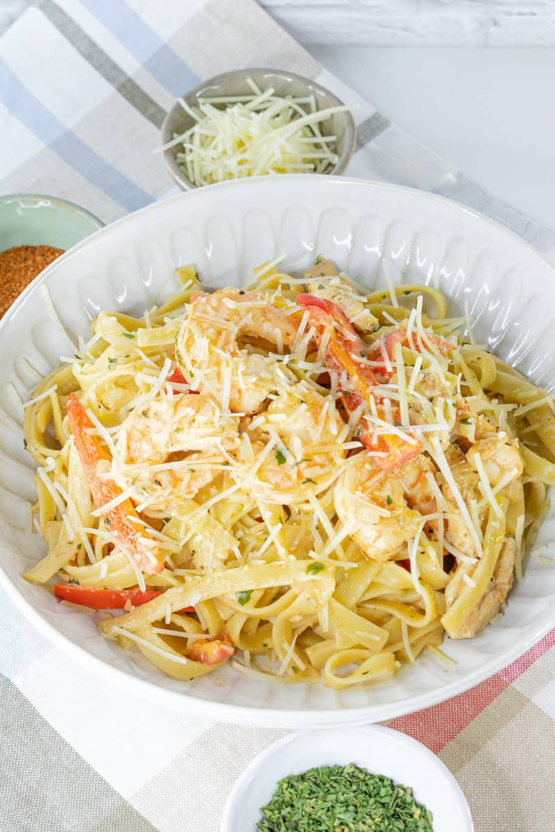 chicken pasta cajun in a bowl with cheese and herbs on the side