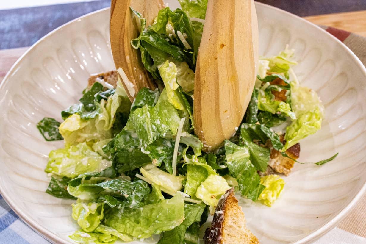 placing Caesar salad in bowl