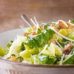 Caesar salad recipe with fork in the bowl