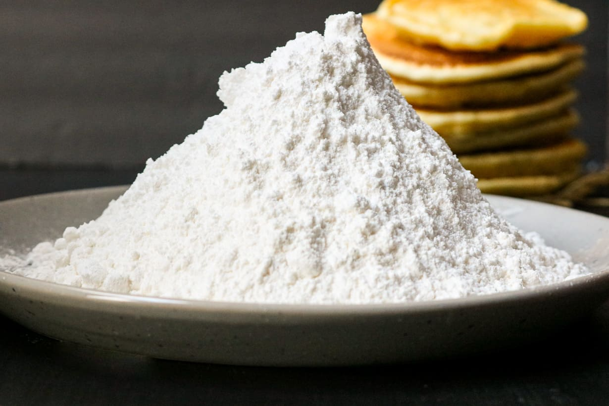 homemade powdered sugar in plate with pancakes in the background