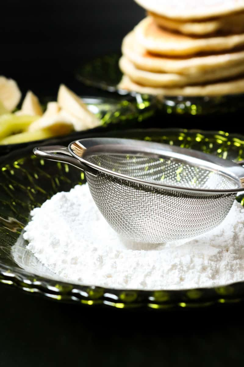 sugar on green plate with sieve