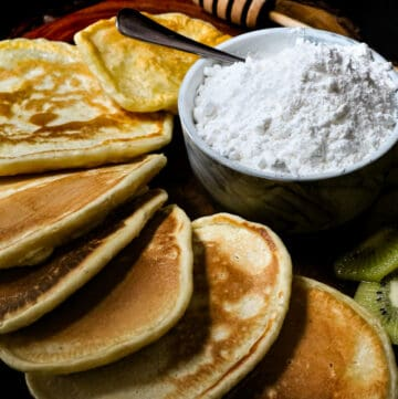 powdered sugar in bowl with spoon and pancakes