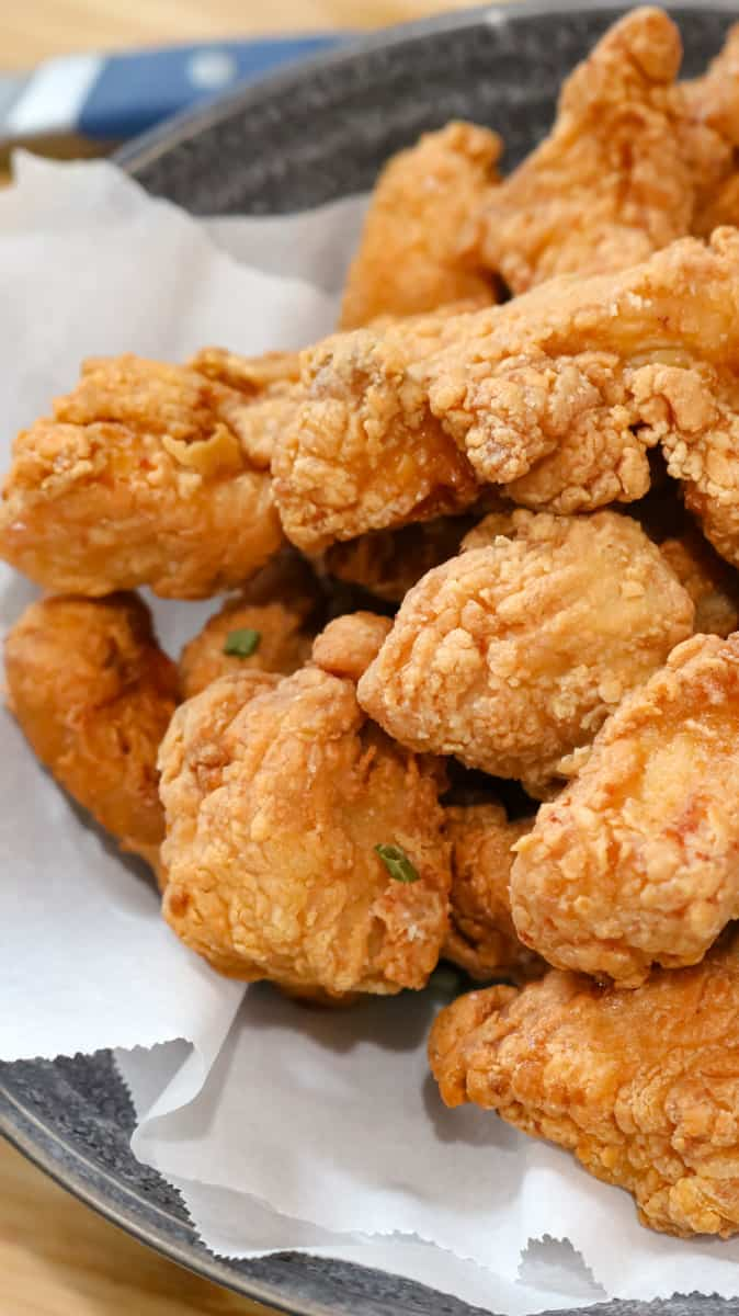 fried chicken in bowl lined with parchment paper