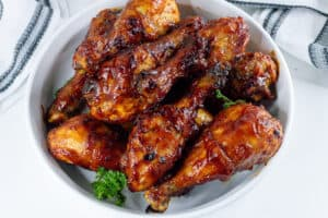 cooked bbq chicken drumsticks in air fryer in white bowl with parsley
