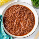 baked beans in brown bowl with corn in the background and parsley