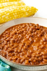 baked beans in brown bowl with corn in the background