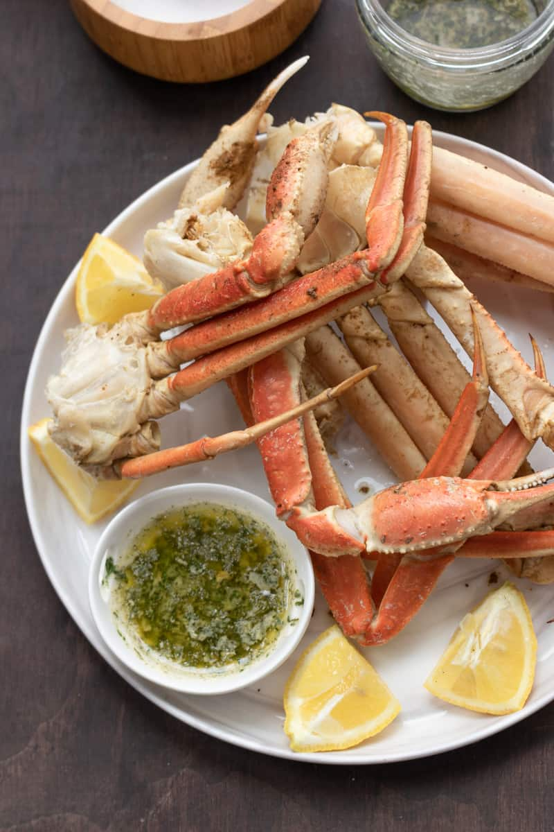 instant pot crab legs on white plate with lemon wedges and garlic butter sauce