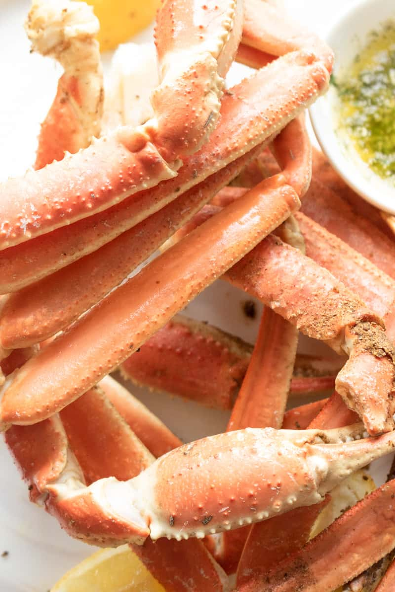 instant pot crab legs on white plate with lemon wedges. 5-minute, succulent, fast, and enjoyable instant pot crab legs with an irresistible butter garlic sauce. Perfect for the summer outings! #instantpotcrablegs #garlicbuttersauce #crablegs #snowcrablegs #savorythoughts