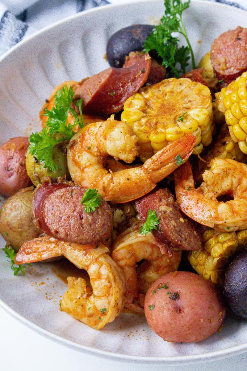 low country shrimp boil in white plate with parsley