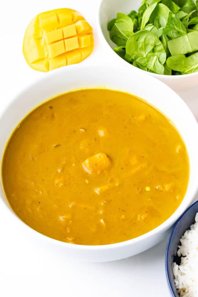 vertical view of mango curry with spinach and mango and rice on white bowl