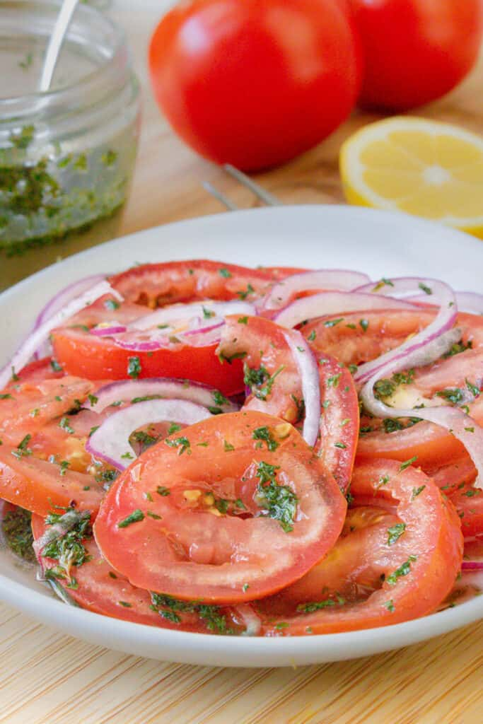 tomatoes and onions in white plate topped with herbs
