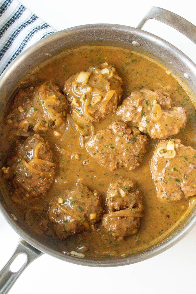 Cooked Salisbury steak with onion gravy in skillet