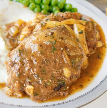 Salisbury steak recipe topped with onions in and gravy in white plate with mashed potatoes and green peas