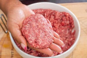 ground beef patty in hand