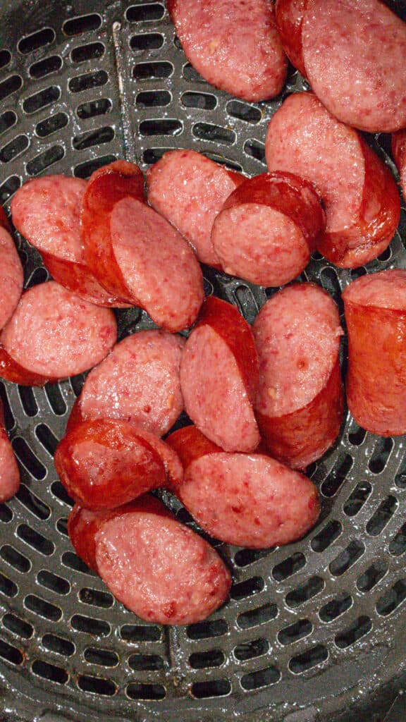 uncooked sausage in air fryer basket