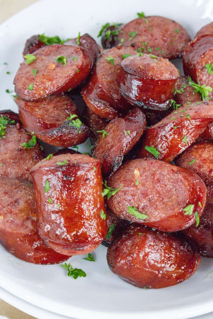 cooked air fryer sausage on white plate topped with fresh parsley flakes